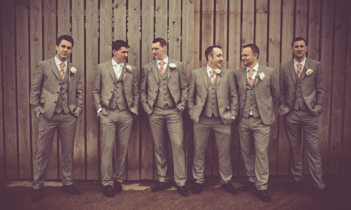 The groomsmen play it cool, lined up in their tweed suits moments before the ceremony