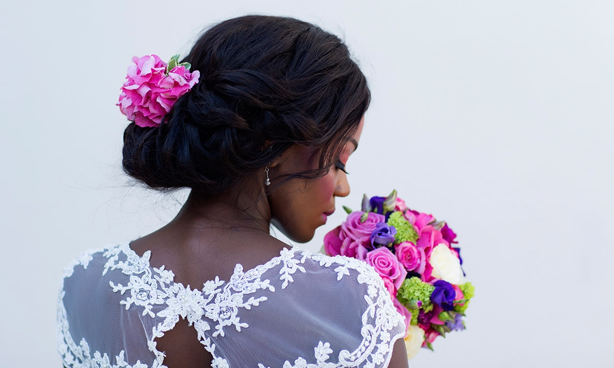 Stunning bride with a colourful purple & pink floral bouquet & lace wedding dress