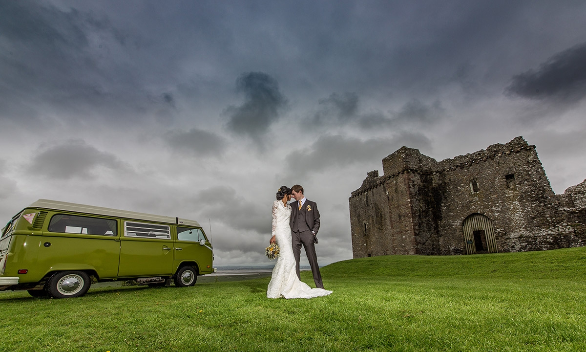 Bride and groom with VW camper van at weobley castle under a dramatic sky, gower wales wedding photography