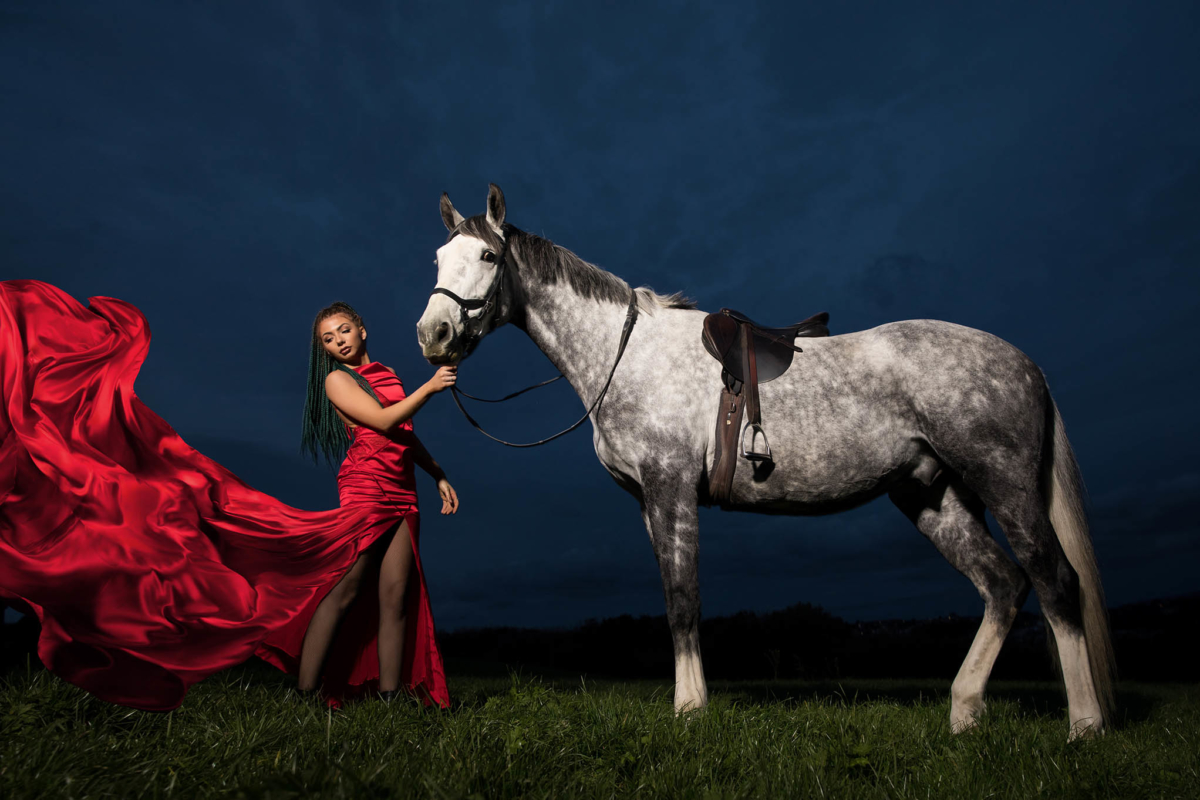 A sunning young lady with her dapple grey horse at dusk with a fashion twist. Her long red dress flows in the wind