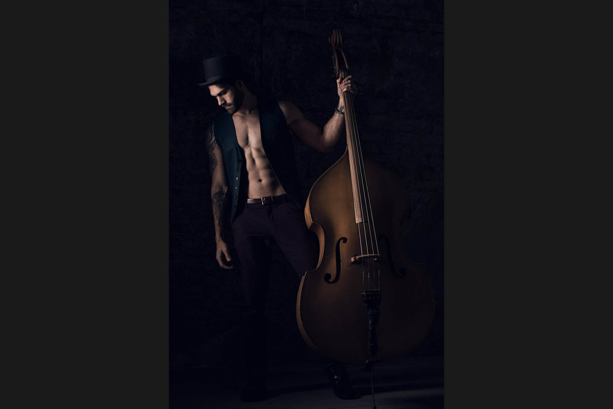 A stylised, dramatically lit image of a tall, handsome guy with top hat & waistcoat holding his double bass